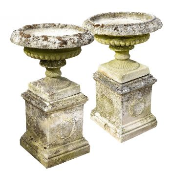 A nicely weathered pair of semi-lobed urns on pedestals